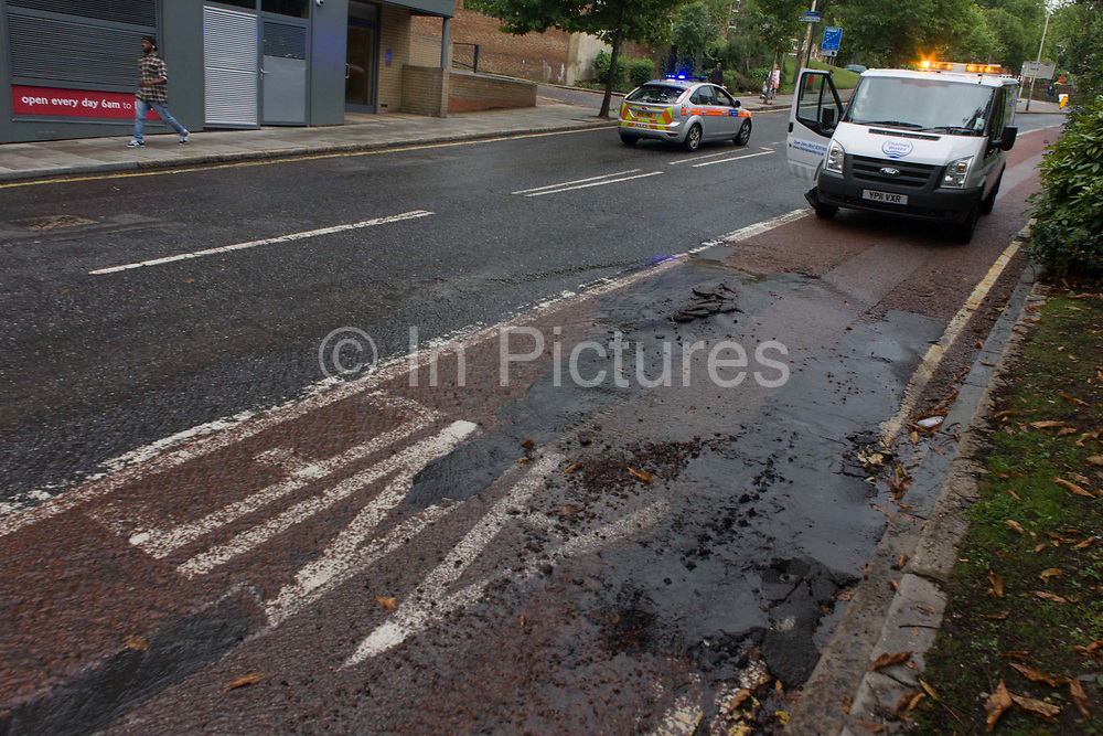 A Thames Water employee at the scene of an empty road due to a cracked road surface of tarmac, weeks after disastrous flooding in nearby Herne Hill, south London. Denmark Hill has been closed in both directions due to another burst water main in multiple locations across the road (A215) between the junctions of Champion Hill and Champion Park in south London. Water is seen running towards Kings College Hospital, 200m downhill and Denmark Hill is a major thoroughfare for the hospital's Accident & Amergency (A&E) department and used by ambulances and emergency traffic throughout the day and night.