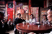 Wu Jian Xin with villagers in a private home discuss the order of events over the  three day Hakka festivities, during the Buddhist religious, festival. Taking tea and smoking,  a favorite pastime, Fujian province, China