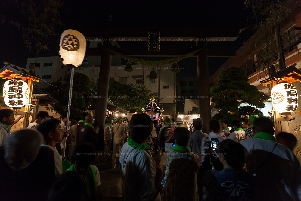 A Mikoshi leaves a shrine under a Torii gate before being  carried through the streets at night during the Hamaorisai matsuri in Chigasaki, Kanagawa, Japan. Monday July 17th 2017. This festival is celebrated on Marine Day in Japan. Over 40 mikoshi (portable shrines) are paraded through the night to arrive on the coast at Southern Beach where they are blessed in a Shintio ritual before being carried into the waves to be purified.