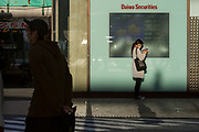 A woman, wearing a surgical mask, checks her smart phone by a window of a bank showing stocks and share prices in a quieter than usual Shibuya, Tokyo, Japan. Thursday May 7th 2020. The month-long state of emergency declared by the Japanese government in response to the COVID-19 pandemic was due to end on May 7th but was extended to May 31st despite Japan appearing to have avoided the high infection and mortality rates of some countries. Areas like Shibuya have many businesses shuttered and closed and the streets are a lot quieter than usual.
