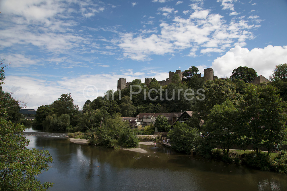 Looking over the River Teme towards Ludlow Castle in Ludlow, United Kingdom. Ludlow is a market town in Shropshire, England. With a population of approximately 11,000, Ludlow is the largest town in south Shropshire. The town is near the confluence of two rivers. The oldest part is the medieval walled town, founded in the late 11th century after the Norman conquest of England. It is centred on a small hill which lies on the eastern bank of a bend of the River Teme. Atop this hill is Ludlow Castle and the parish church, St Laurences, the largest in the county. From there the streets slope downward to the River Teme.
