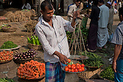 A vendor weighs tomatoes on scales at a market in Dhaka, Bangladesh.