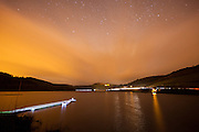 Ladybower Reservoir at night. The largest body of water in the Peak District captured with car light trails, stars and a torch lit jetty.