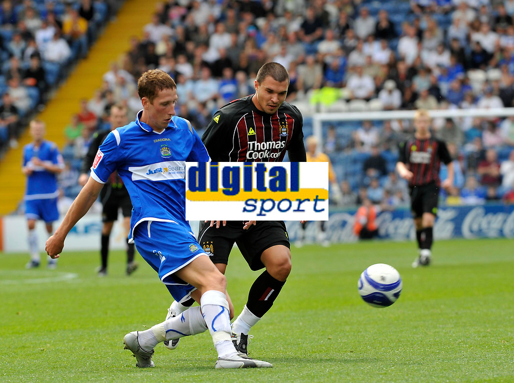 Stockport's Jimmy McNulty (L) clears the ball under pressure from Manchester City's Valeri Bojinov<br />Photo: Paul Greenwood/Richard Lane Photography. Stockport County v Manchester City. Pre Season Friendy. 02/08/2008.