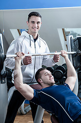 Coach supporting man in gym doing weight training