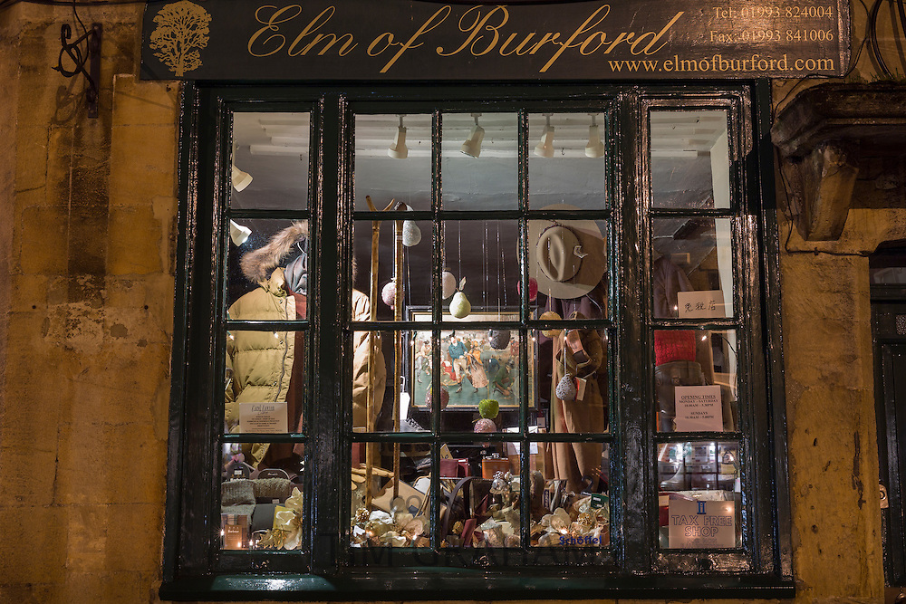 Window display of old traditional country clothing shop, Elm of Burford, on Burford High Street at night, The Cotswolds