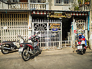 "27 MAY 2015 - BANGKOK, THAILAND: The entrance to Ajarn Neng Onnut's home / tattoo studio in Bangkok. Ajarn Neng is a revered master of sacred tattoos and sees people all day at his Bangkok home. Sak Yant (Thai for ""tattoos of mystical drawings"" sak=tattoo, yantra=mystical drawing) tattoos are popular throughout Thailand, Cambodia, Laos and Myanmar. The tattoos are believed to impart magical powers to the people who have them. People get the tattoos to address specific needs. For example, a business person would get a tattoo to make his business successful, and a soldier would get a tattoo to help him in battle. The tattoos are blessed by monks or people who have magical powers. Ajarn Neng, a revered tattoo master in Bangkok, uses stainless steel needles to tattoo, other tattoo masters use bamboo needles. The tattoos are growing in popularity with tourists, but Thai religious leaders try to discourage tattoo masters from giving tourists tattoos for ornamental reasons.     PHOTO BY JACK KURTZ"