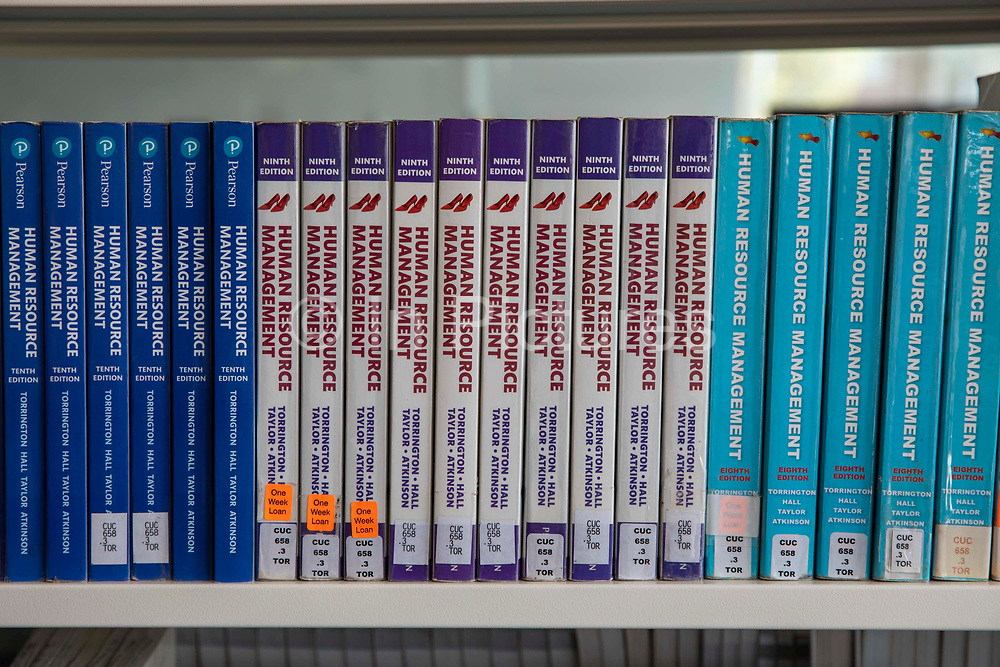 Business study library books on a shelf in a university library on the 28th of April 2021, Coventry, United Kingdom. Shelves full of books about business management, making better decisions, project management and making business better.