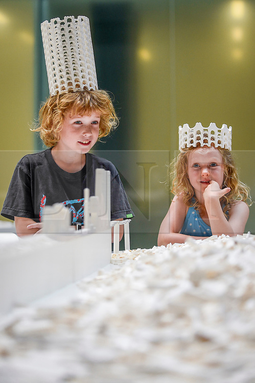 """© Licensed to London News Pictures. 26/07/2019. LONDON, UK. Hunter Tagholm, aged 8 (L), and Willow Beal, aged 5 (R), pose with a Lego crown at the preview of """"The cubic structural evolution project"""", 2004, by Olafur Eliasson at Tate Modern.  Exhibited for the first time in the UK, the artwork comprises one tonne of white Lego bricks inspiring visitors to create their own architectural vision for a future city and is on display until 18 August 2019.  The work coincides with the artist's new retrospective exhibition """"In real life"""" at Tate Modern on display to 5 January 2020. (Parental permission to photograph obtained). Photo credit: Stephen Chung/LNP"""