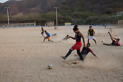 Young Colombians people male and female playig football in the sand at dusk, Taganga, Colombia.
