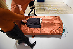 "© Licensed to London News Pictures. 29/10/2019. LONDON, UK. A staff member experiences ""Shroud/Chrysalis I"" by Catherine Richards, a copper sheet that cuts out mobile phone signals. Preview of ""24/7: A Wake-Up Call For Our Non-Stop World"", a new exhibition opening on 31 October at Somerset House.  The show examines our inability to switch off from our 24/7 culture.  Over 50 multi-disciplinary works explore the pressure to produce and consume information around the clock. taking visitors on a 24-hour cycle from dawn to dusk through interactive installations.  Photo credit: Stephen Chung/LNP"