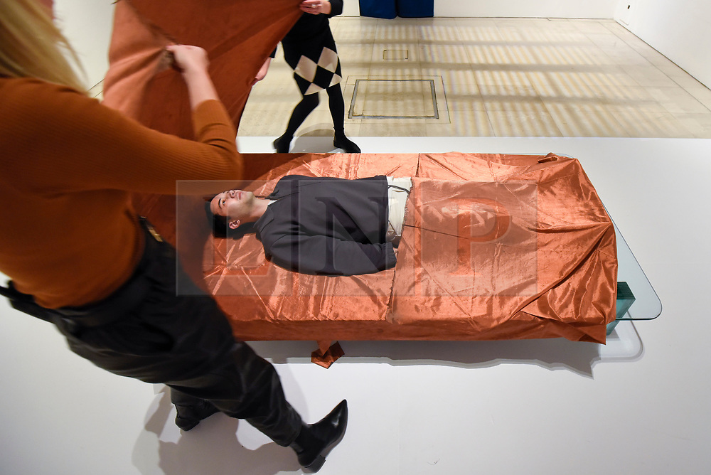 """© Licensed to London News Pictures. 29/10/2019. LONDON, UK. A staff member experiences """"Shroud/Chrysalis I"""" by Catherine Richards, a copper sheet that cuts out mobile phone signals. Preview of """"24/7: A Wake-Up Call For Our Non-Stop World"""", a new exhibition opening on 31 October at Somerset House.  The show examines our inability to switch off from our 24/7 culture.  Over 50 multi-disciplinary works explore the pressure to produce and consume information around the clock. taking visitors on a 24-hour cycle from dawn to dusk through interactive installations.  Photo credit: Stephen Chung/LNP"""