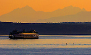 The Olympic Mountains create the backdrop as a Washington State ferry makes its way past two paddle boarders during its voyage between Edmonds and Kingston during sunset.<br />