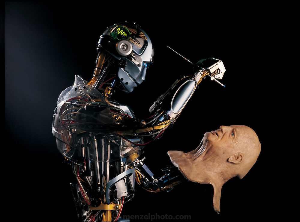 Wielding a paint brush, a robot touches up its human master in this photo-illustration at the SARCOS robot company in Salt Lake City, UT. From the book Robo sapiens: Evolution of a New Species, page 20-21.