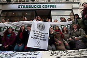 Conduit Street off Regent Street. UK Uncut flashmob occupy Starbucks to draw attention to the fact that they have paid no corporation tax for the last three years, and that the tax that rich companies haven't paid, would pay for the cuts the government is making to public services. Protesters hold a sign saying 74% of £15 billion benefit cuts taken from women's income.