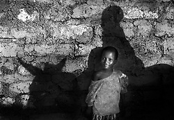 Khady rests in the shade as her brother takes the doneky to the market in the village of Dembel Jumpora, Guinea Bissau, West Africa.