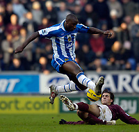 Photo: Jed Wee.<br />Wigan Athletic v Arsenal. The Barclays Premiership.<br />19/11/2005.<br />Wigan's Jason Roberts hurdles over a challenge from Arsenal's Cesc Fabregas.