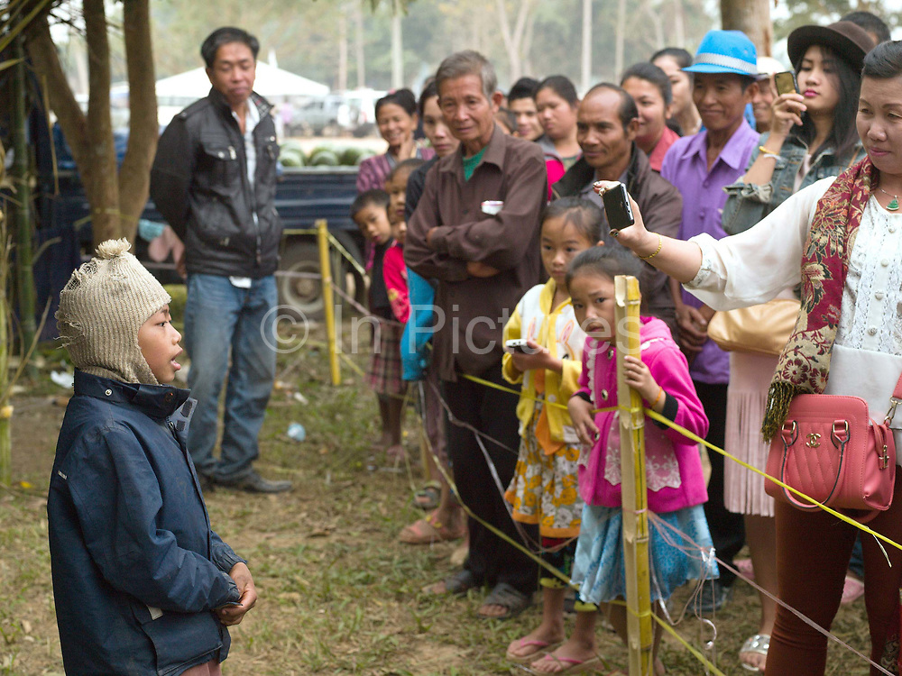 A Yumbri ethnic minority boy sings a song in front of a crowd of Lao tourists at the Sayaboury elephant festival, Sayaboury province, Lao PDR. The Yumbri, otherwise known as Yellow Leaves, Tong Luang or Mlabri are the last remaining hunter-gatherer Austroasiatic-speaking community living in the primary forests and river basins of the Nam Poui region in Sayaboury province. They are Laos smallest ethnic group with estimates of the numbers of Yumbri remaining varying between 21 and 30 individuals.