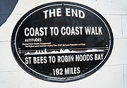 THE END sign for England Coast to Coast Walk, at Robin Hood's Bay, on the North Sea, North York Moors National Park, North Yorkshire county, England, UK, Europe. On our England Coast to Coast hike day 13 of 14, we went from Grosmont to Robin Hood's Bay on foot and via van.  We walked a rural path through bracken, purple blooming heather moors, and farmland before descending cliffs to the beach and village of Robin Hood's Bay. We dipped our boots into the North Sea, having completed our journey via foot and car from the Irish Sea over two weeks. Lunch at Wainwrights Bar at the Bay Hotel. [This image, commissioned by Wilderness Travel, is not available to any other agency providing group travel in the UK, but may otherwise be licensable from Tom Dempsey – please inquire at PhotoSeek.com.]