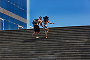 Couple running up the steps behind the W hotel Barcelonetta, the port area of, Barcelona, Spain.