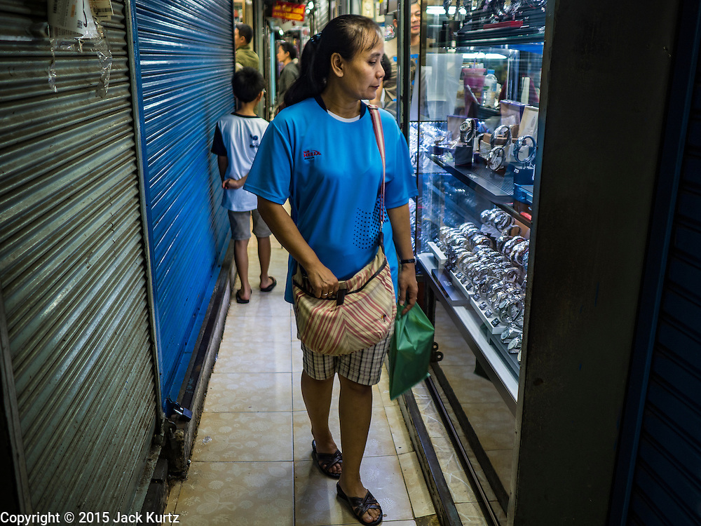 11 OCTOBER 2015 - BANGKOK, THAILAND: Men walk through Saphan Lek market on what Bangkok city government is saying is the last day of business for the market. Many shops in the market are already closed. Street vendors and illegal market vendors in the Saphan Lek area will be removed in the next two weeks as a part of an urban renewal project coordinated by the Bangkok Metropolitan Administration. About 500 vendors along Damrongsathit Bridge, popularly known as Saphan Lek, have until Monday, October 11,  to relocate. Vendors who don't move will be evicted. Saphan Lek is one of several markets and street vending areas being closed in Bangkok this year. The market is known for toy and replica guns, bootleg and pirated DVDs and CDs and electronic toys.    PHOTO BY JACK KURTZ OCTOBER 2015 - BANGKOK, THAILAND: A woman looks at watches for sale on what Bangkok city government is saying is the last day of business for Saphan Lek Market. Many shops in the market are already closed. Street vendors and illegal market vendors in the Saphan Lek area will be removed in the next two weeks as a part of an urban renewal project coordinated by the Bangkok Metropolitan Administration. About 500 vendors along Damrongsathit Bridge, popularly known as Saphan Lek, have until Monday, October 11,  to relocate. Vendors who don't move will be evicted. Saphan Lek is one of several markets and street vending areas being closed in Bangkok this year. The market is known for toy and replica guns, bootleg and pirated DVDs and CDs and electronic toys.    PHOTO BY JACK KURTZ