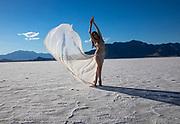 Photo of a nude woman posing on the Bonneville Salt Flats, Utah waving a long scarf
