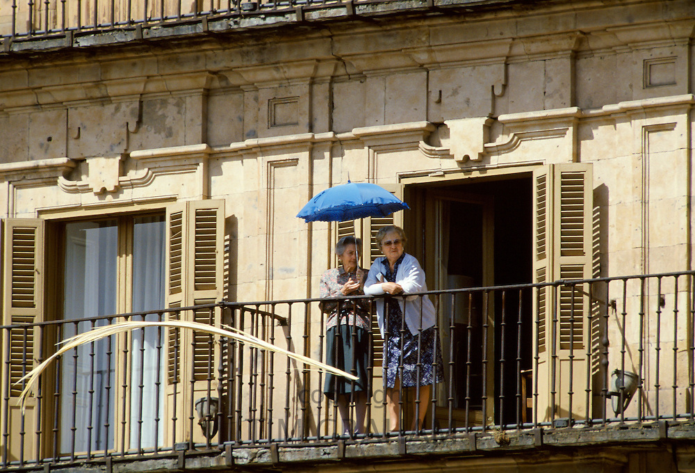 Elderly women watching from a balcony with umbrella for sun protection in Portugal
