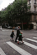 Champs Elysees. Father crosses the street with his two young children. His son holds a toy gun. Paris, France.