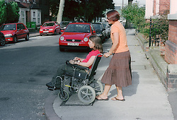 Woman trying to manoeuvre wheelchair down the kerb in order to cross the road,