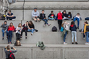 Young visitors to the capital sit beneath Nelson's Column with a view across Trafalgar Square, on 20th May 2019, in London, England.