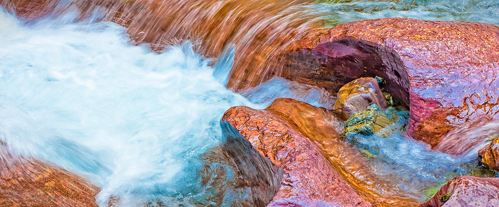 Rushing water carves path through colored rocks at Avalanche Gorge, Glacier National Park, Montana.