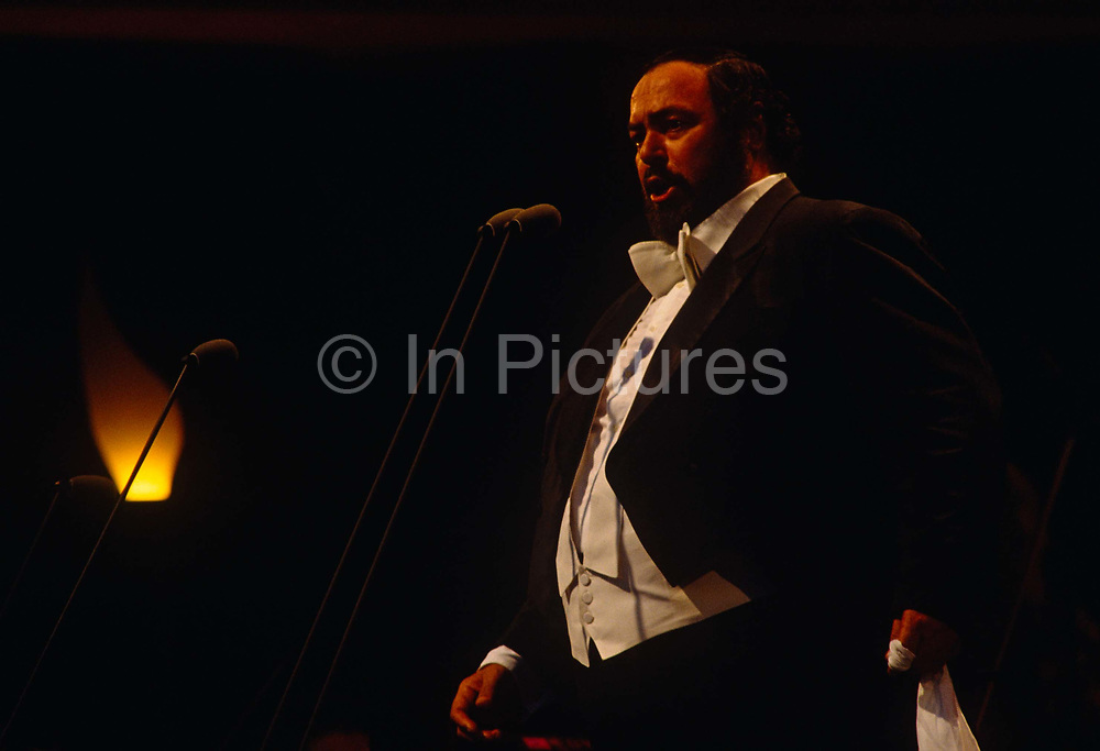 The Italian operatic tenor Luciano Pavarotti performs in London during the free Party in the Park concert to celebrate his 30 years in opera. A crowd of 100,000 stood in the London rain to watch Pavarotti perform 20 arias by Verdi, Puccini, Bizet and Wagner. VIPs the Princess of Wales, Prime Minister John Major and Michael Caine got soaked in heavy rain along with everyone else sitting on the grass cowering beneath tarpaulins. We see the rotund Operatic maestro in full flow, belting out an aria while dressed in formal tails and wastecoat and holding his customary scarf that he uses to dab the sweat from his brow. Pavarotti helped bring an otherwise high-brow artform to the ordinary Man after the BBC used his rendition of Nessun Dorma to theme their World Cup TV coverage. This lead the way to Opera reaching the Common Man in Britain.