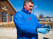 """20 MARCH 2020 - DES MOINES, IOWA: CHAD BUSH carries hand sanitizer to a waiting car at the Foundry, a distillery in Des Moines. The distillery suspended its distilling operations to make hand sanitizer this week. They distributed it free to people who came to their building. On Friday thousands of people came to get some. There line was more than one mile long. On Friday morning, 20 March, Iowa reported 45 confirmed cases of the Coronavirus. Restaurants, bars, movie theaters, places that draw crowds are closed for at least 30 days. There are no """"shelter in place"""" orders in effect anywhere in Iowa but people are being encouraged to practice """"social distancing"""" and many businesses are requiring or encouraging employees to telecommute.         PHOTO BY JACK KURTZ"""