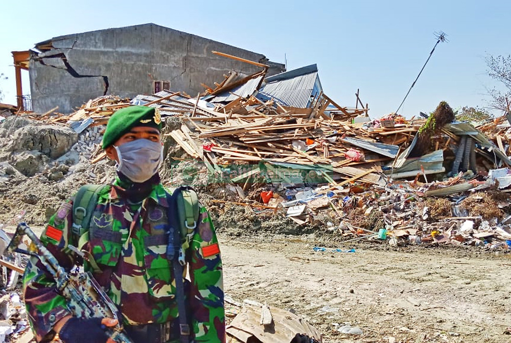 October 3, 2018 - Palu, Central Sulawesi, Indonesia - PALU, INDONESIA - OCTOBER 03, 2018 : an Indonesia military is guarding the location of movable land that emits mud at Petobo Village on October 03, 2018 in Palu, Central Sulawesi Province, Indonesia. The guard was equipped with long-barreled weapons to guard against looting in the homes of the victims after the earthquake and tsunami in Central Sulawesi on September 28, 2018. (Credit Image: © Sijori Images via ZUMA Wire)