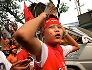 A young boy chants and dance in the streets of Mandalay. Myanmar, 2012.