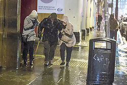 © Licensed to London News Pictures . 12/02/2014 . Manchester , UK . People struggle against extremely high winds and biting rain in Manchester City Centre this evening (12th February 2014) as the Met Office announces a Red weather warning for the region . Photo credit : Joel Goodman/LNP
