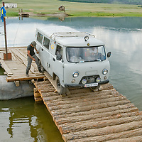 MONGOLIA. A van used by an archaeology expedition unloads from wooden ferry across a river between Rinchenlhumbe and Tsaagan Nuur.
