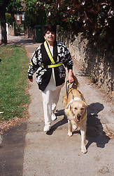 Woman with visual impairment walking along street with guide dog,