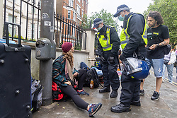Licensed to London News Pictures. 17/06/2021. London, UK. Protesters where left on the pavement with their possessions as police and bailiffs clear an anti-lockdown camp on Shepherd's Bush Green this morning. The demonstrators who have been camping on the green since 31 May 2021 were forced out of their tents this morning with many of their possessions left behind as police in riot gear and on horseback forced everyone out of the west London green space. The protesters have been demonstrating against lockdown, mask wearing, vaccines and testing. Photo credit: Alex Lentati/LNP