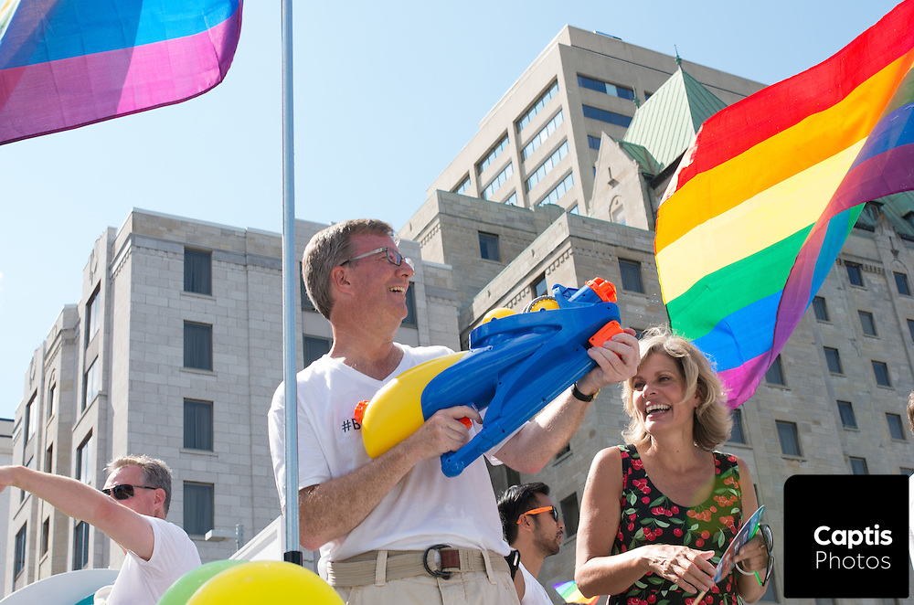 Ottawa mayor Jim Watson holds a water gun while riding a float in the parade. August 24, 2014.