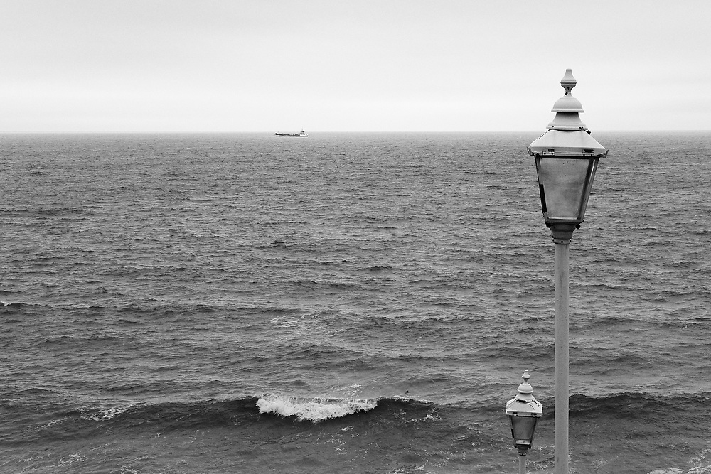 A boat sits on the horizon opposite Cromer in North Norfolk. Looking from above the Esplanade east of the pier, a couple of lamp posts puncher the scene.<br /> <br /> Photo by Jonathan J Fussell, COPYRIGHT 2021