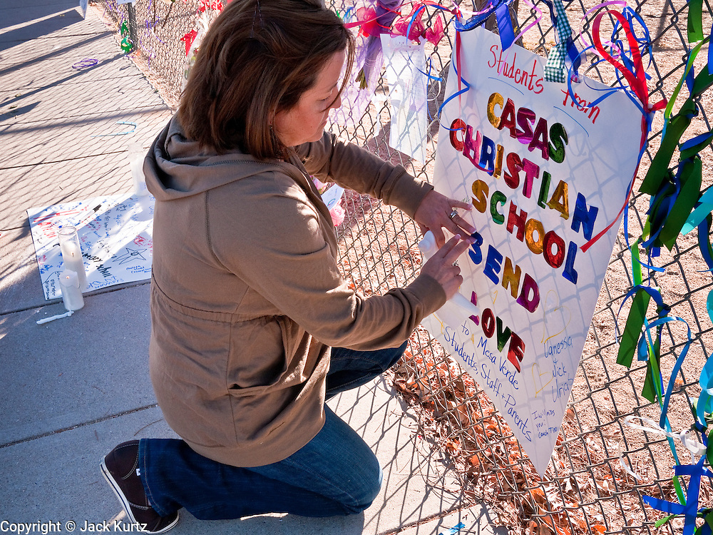 tucsonshooting - 10 JANUARY 2011 - ORO VALLEY, AZ: Renee Lustenberger (CQ) a teacher at Casas Christian School, puts up a card for Christina Green, who was killed in the mass shooting Saturday,  at Mesa Verde Elementary School in Oro Valley. Christina Green was a student at Mesa Verde.  ARIZONA REPUBLIC PHOTO BY JACK KURTZ..Gabrielle Giffords shooting
