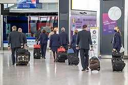 """© Licensed to London News Pictures. 09/04/2021. London, UK. Flight attendants walk through Heathrow Terminal 5. Today, Transport Secretary Grant Shapps sets out details of the government's """"traffic Light"""" system for May 17th so that the public can travel abroad with passengers requiring to take a private covid-19 test each way, costing as much as £150.00 for one test. Photo credit: Alex Lentati/LNP"""
