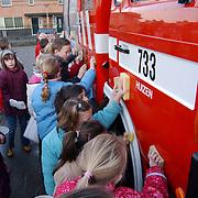 Kinderen van eholbothschool Huizen wassen auto's.brandweer, brandweerwagen, scholieren, water, koud, spons, sponzen,