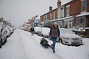 Young people out with their slegde in Kings Heath head out to enjoy the heavy snow fall on Sunday 10th December 2017 in Birmingham, United Kingdom. Deep snow arrived in much of the UK, closing roads and making driving treacherous, while many people simply enjoyed the weather.