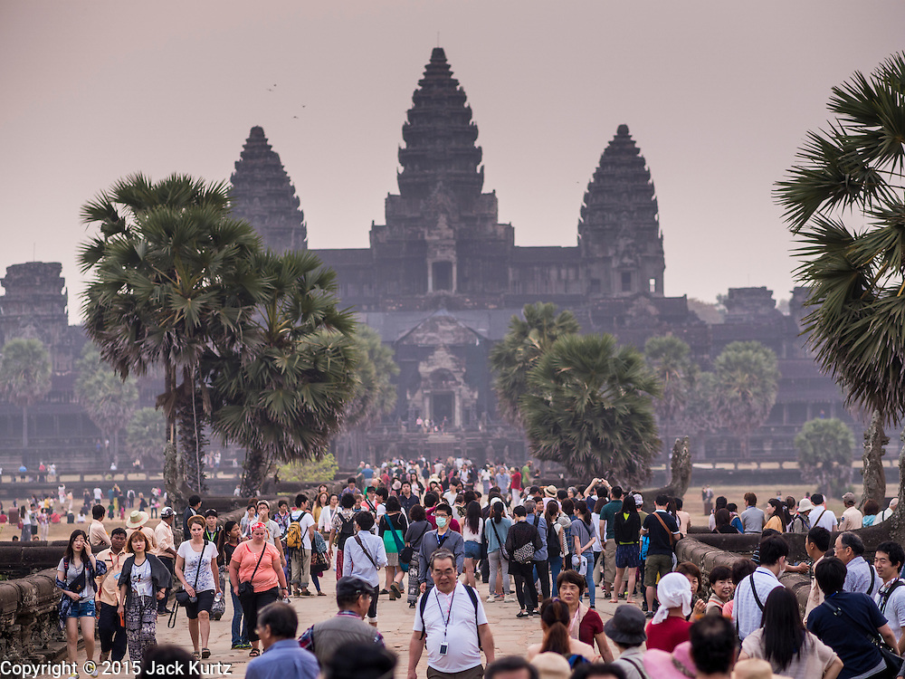 """14 MARCH 2105 - SIEM REAP, SIEM REAP, CAMBODIA: Tourists walk into the area around Angkor Wat. The area known as """"Angkor Wat"""" is a sprawling collection of archeological ruins and temples. The area was developed by ancient Khmer (Cambodian) Kings starting as early as 1150 CE and renovated and expanded around 1180CE by Jayavarman VII. Angkor Wat is now considered the seventh wonder of the world and is Cambodia's most important tourist attraction.   PHOTO BY JACK KURTZ"""