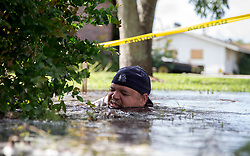 September 11, 2017 - Belle Glade, Florida, U.S. - Palm Beach County Public works employee Felix Riveira struggles to put a patch on a broken water main adding to the flooding at SE 6th Drive in Belle Glade , Florida on September 11, 2017. (Credit Image: © Allen Eyestone/The Palm Beach Post via ZUMA Wire)
