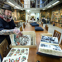 Nederland, Amsterdam , 27 oktober 2011..Tattoo koning Henk Schiffmacher tussen zijn verzameling tekeningen en foto's van Tattoos bestemd voor het  Tattoo Museum van op de Plantage Middenlaan nr 62..Amsterdam Tattoo Museum and the most famous Dutch tattoo-artist Henk Schiffmacher with his historical materials.