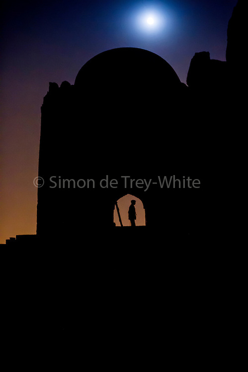"4th December 2014, New Delhi, India. Moonrise over the ruins of Feroz Shah Kotla as people come to make offerings to Djinns in the hopes of getting wishes granted, New Delhi, India on the 4th December 2014<br /> <br /> PHOTOGRAPH BY AND COPYRIGHT OF SIMON DE TREY-WHITE a photographer in delhi<br /> + 91 98103 99809. Email: simon@simondetreywhite.com<br /> <br /> People have been coming to Firoz Shah Kotla to leave written notes and offerings for Djinns in the hopes of getting wishes granted since the late 1970's. Jinn, jann or djinn are supernatural creatures in Islamic mythology as well as pre-Islamic Arabian mythology. They are mentioned frequently in the Quran  and other Islamic texts and inhabit an unseen world called Djinnestan. In Islamic theology jinn are said to be creatures with free will, made from smokeless fire by Allah as humans were made of clay, among other things. According to the Quran, jinn have free will, and Iblis abused this freedom in front of Allah by refusing to bow to Adam when Allah ordered angels and jinn to do so. For disobeying Allah, Iblis was expelled from Paradise and called ""Shaytan"" (Satan).They are usually invisible to humans, but humans do appear clearly to jinn, as they can possess them. Like humans, jinn will also be judged on the Day of Judgment and will be sent to Paradise or Hell according to their deeds. Feroz Shah Tughlaq (r. 1351–88), the Sultan of Delhi, established the fortified city of Ferozabad in 1354, as the new capital of the Delhi Sultanate, and included in it the site of the present Feroz Shah Kotla. Kotla literally means fortress or citadel."