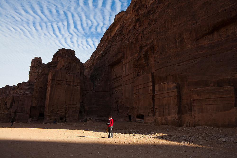 Leora Leshem, lit by a beam of light, stands in the Street of Facades in Petra, Jordan.